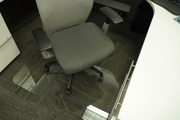 gray rolling office chair at desk with glass floor mat underneath