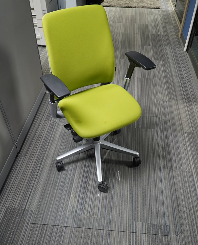 green rolling office chair with glass floor mat underneath