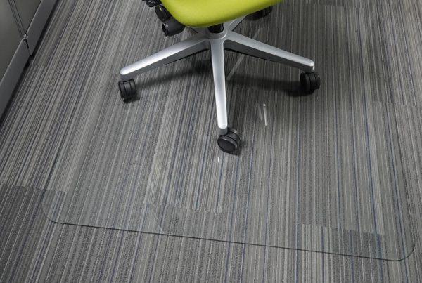 glass chair mat under green rolling office chair